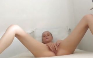 Blonde cutie naked on the bed masturbating playfully