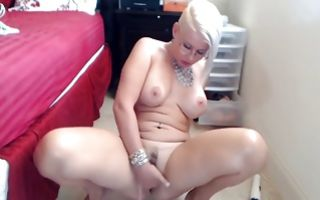 Raunchy blonde milf with fake tits fucks her cunt in solo